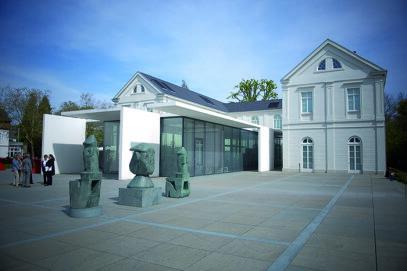 Max Ernst Museum Brühl des LVR (Seitliche Außenansicht des Max Ernst Museums Brühl des LVR mit drei Skulpturen im Vordergrund.)